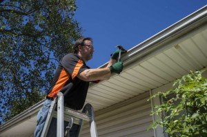 Repairman fixing gutters
